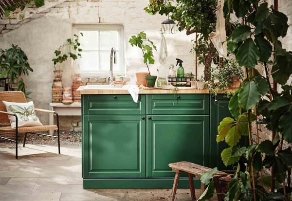 Une cuisine ensoleillée remplie de plantes et meublée d'un comptoir aux superbes façades vertes.