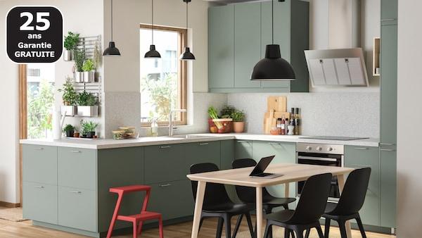 Une cuisine gris-vert, une table en bois, des chaises noires, une suspension noire et beaucoup d'herbes aromatiques suspendues à des rails.