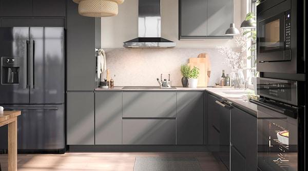 Une cuisine grise moderne avec des appareils électroménagers en acier inoxydable noir