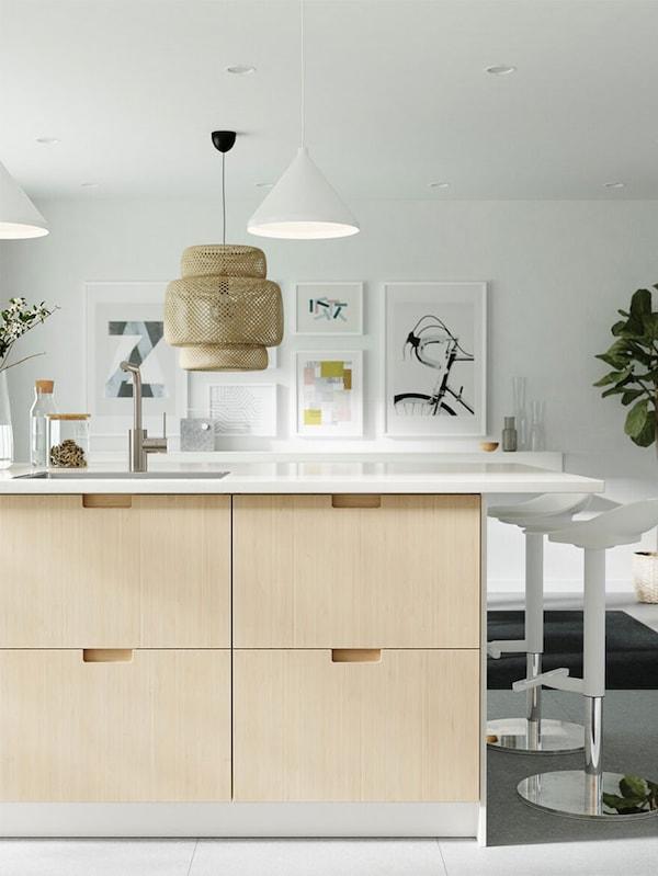 Une cuisine illuminée dans laquelle se trouve un îlot pourvu de façades de porte en bambou, un comptoir en quartz et des tabourets de bar