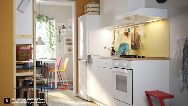 Une cuisine KNOXHULT blanche, un marchepied rouge, une étagère en pin, des dessertes noires et des chaises de cuisine colorées.