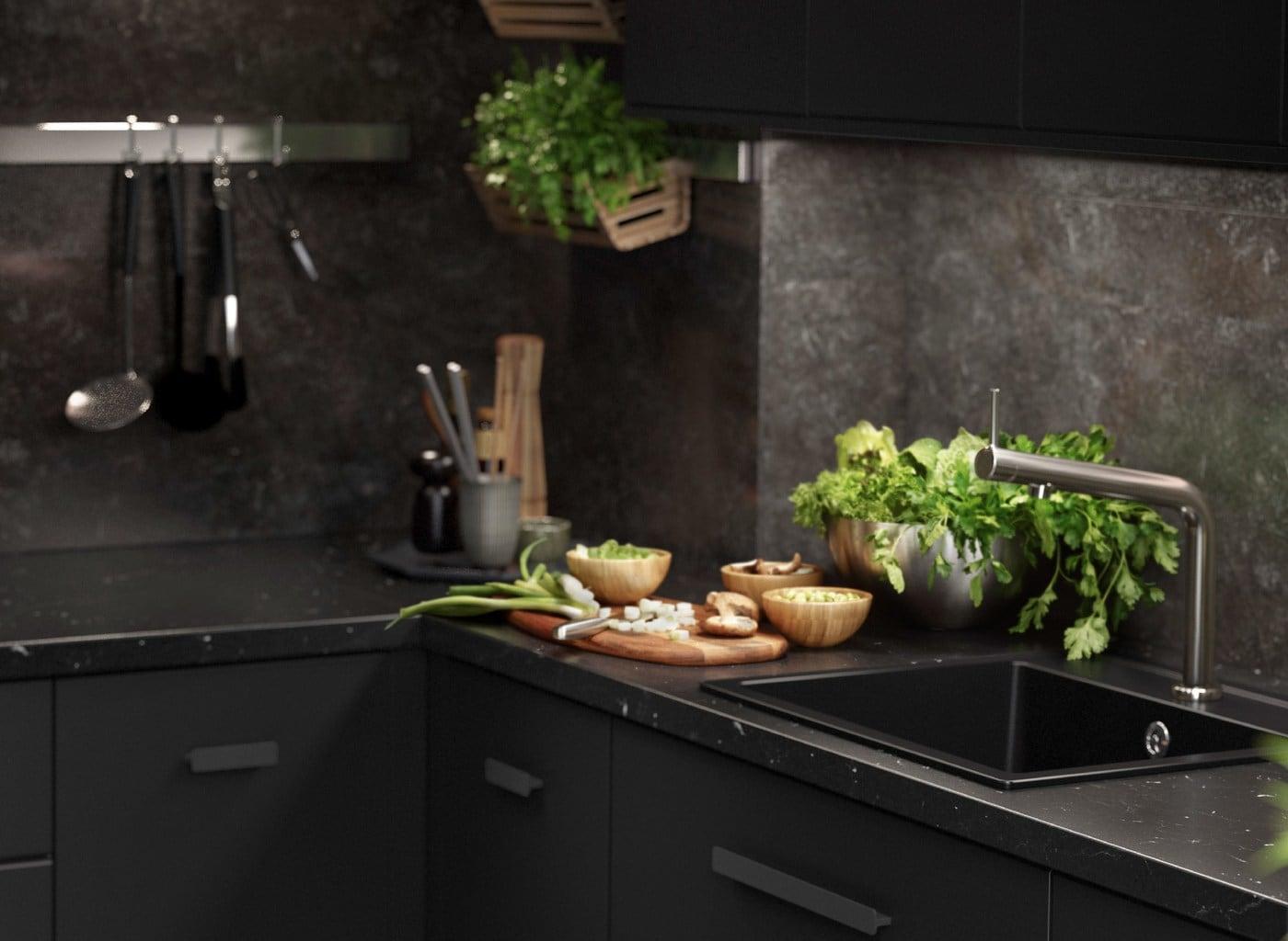 Une cuisine KUNGSBACKA noire avec des éléments effet marbre, des ustensiles de cuisine et des herbes fraîches.