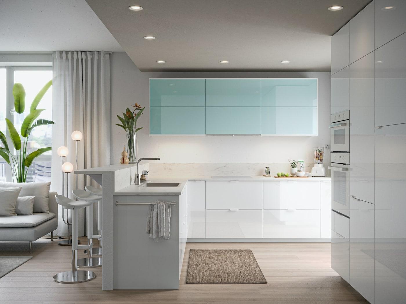 Une cuisine minimaliste avec des portes blanches brillantes et turquoises, une planche à découper avec des fruits, un mixeur avec des fruits.