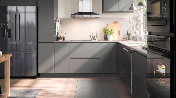 Une cuisine moderne grise avec des électroménagers en acier inoxydable noir