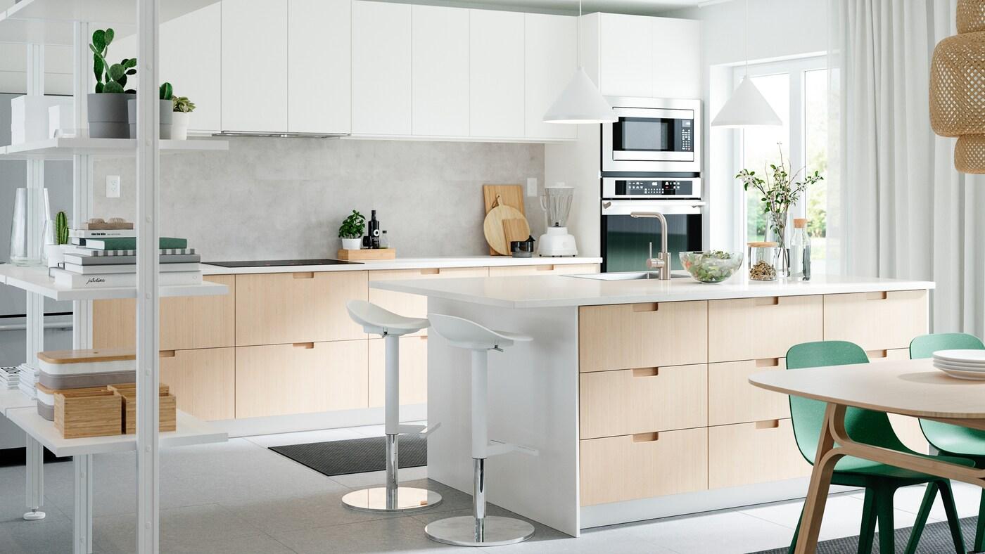 Une cuisine munie de façades de tiroir et de portes blanches ou en bambou, un îlot de cuisine, deux tabourets de bar, deux suspensions et des chaises vertes.