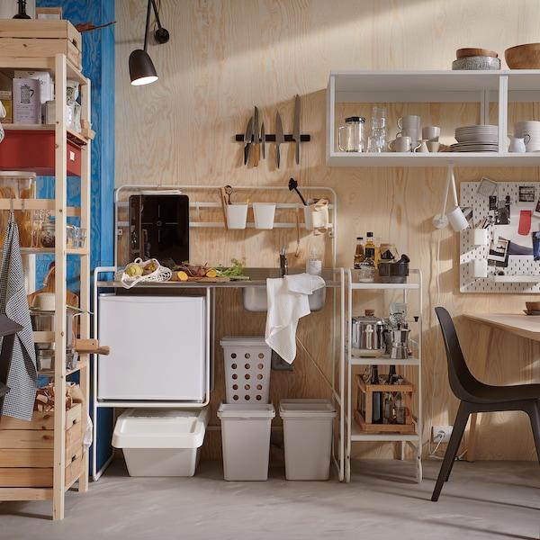 Une cuisine petite mais lumineuse avec mini-cuisine SUNNERSTA, bacs de tri des déchets en gris, système de rangement en pin et chaises noires.