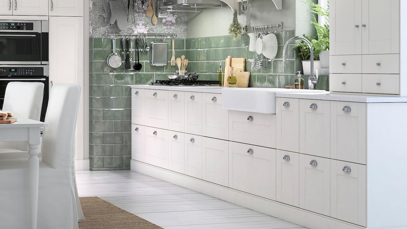 Une cuisine verte et blanche avec 18tiroirs de cuisine blancs aux poignées arrondies chromées et une armoire murale blanche.