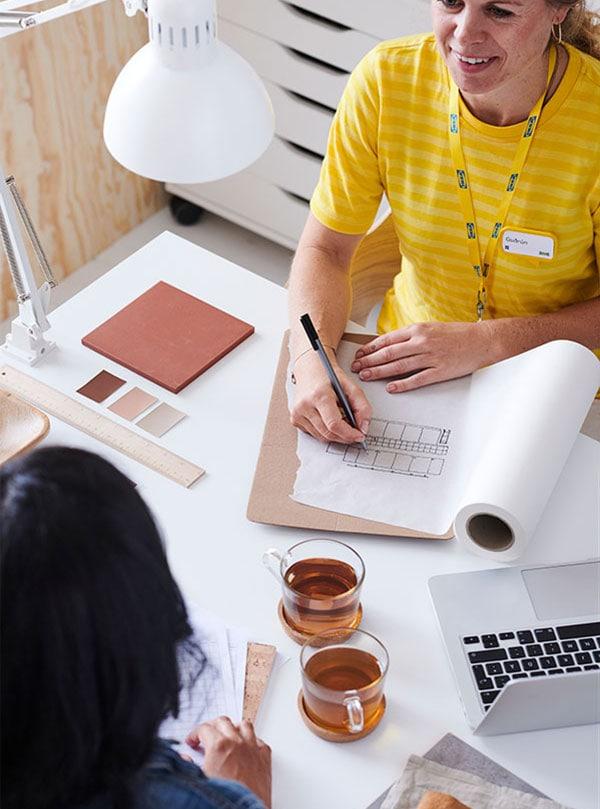 Une designer d'intérieur fait la planification d'une pièce en compagnie d'une cliente.
