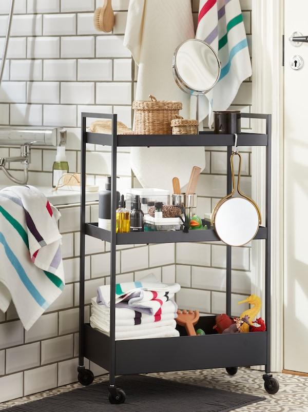 Une desserte noire NISSAFORS en acier, avec trois tablettes remplies de serviettes et de jouets de bain, placée devant une baignoire.