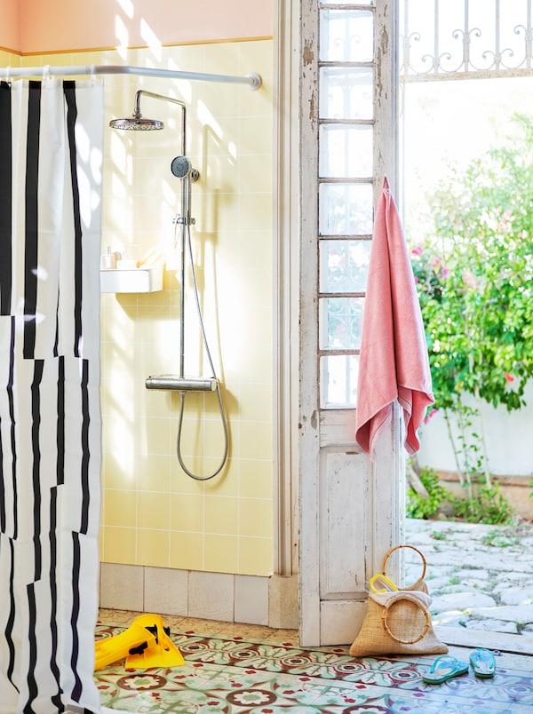 Une douche ouverte avec un rideau de douche noir et blanc, à côté d'une porte ouverte en bois blanc patiné.