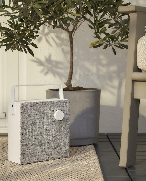 Une enceinte sans fil en blanc/gris, de forme carrée et avec poignée, sur un tapis beige à côté d'un fauteuil d'extérieur gris.
