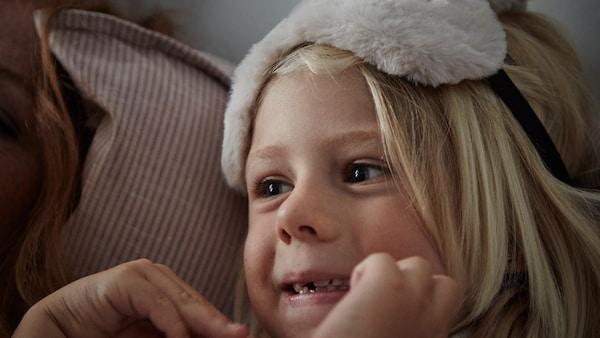 Une enfant aux longs cheveux blonds est couchée sur un oreiller souple. Elle a un masque de nuit duveteux sur la tête.