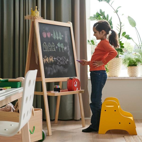 Une enfant debout devant un tableau noir sur un chevalet, tenant une craie dans la main.