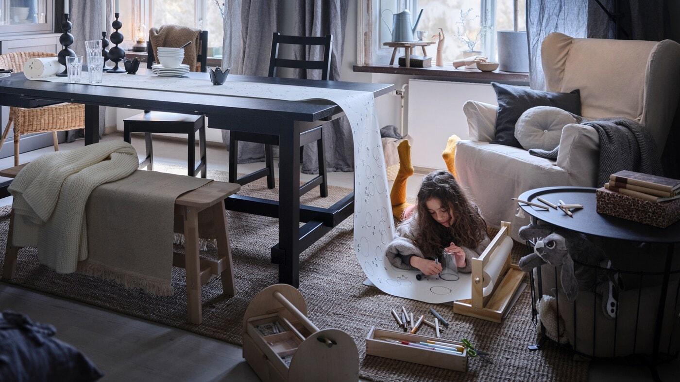 Une enfant étendue sur un tapis couvrant le plancher dessine sur un rouleau de papier dont l'une des extrémités a été tirée sur une table à rallonge NORDVIKEN de couleur noire.