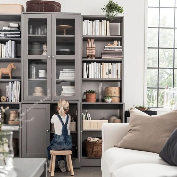 Une enfant regardant à l'intérieur d'une grande armoire grise avec portes vitrées, dans un salon.