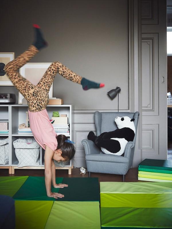 Une enfant se tenant sur les mains sur un tapis de gymnastique vert pliant.