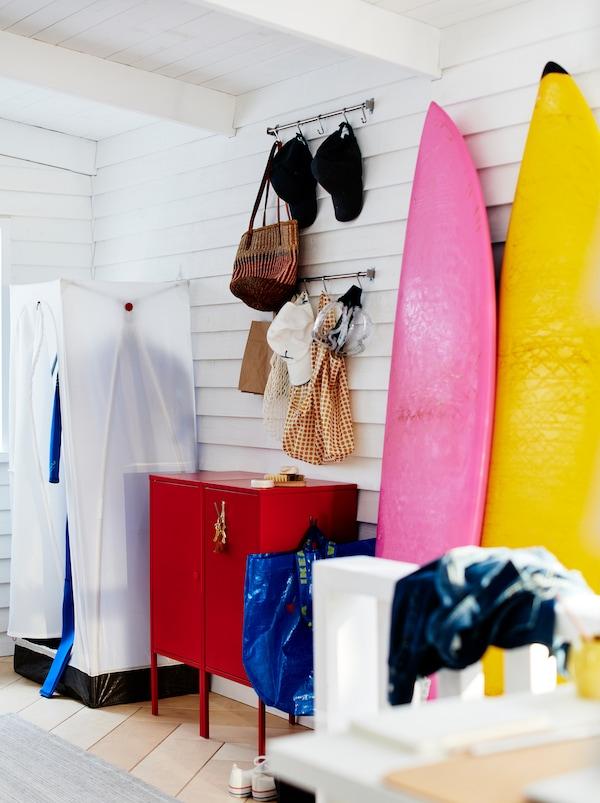 Une entrée au style décontracté avec une armoire-penderie VUKU et une commode LIXHULT rouge.