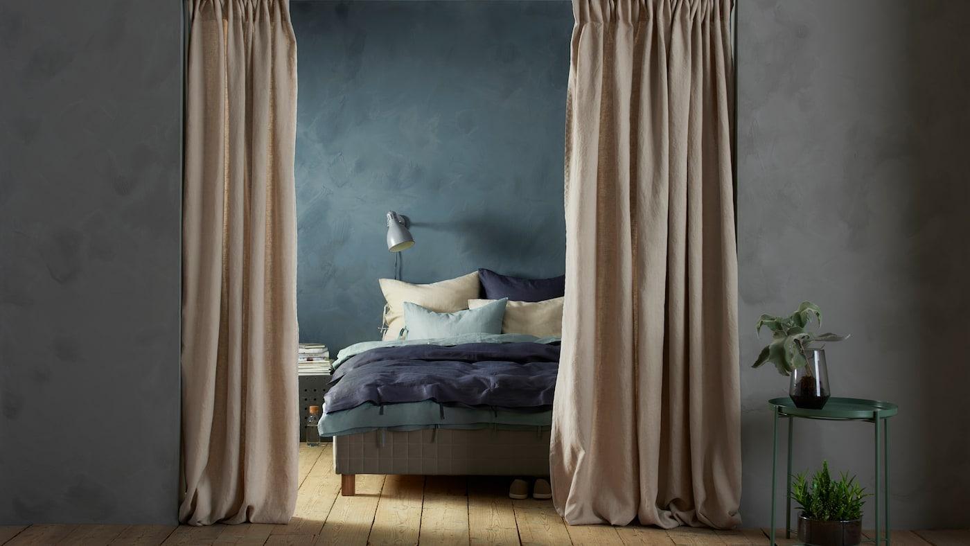 Une entrée avec des rideaux beiges ouverts AINA qui y sont suspendus. Au-delà de l'entrée se trouve un lit avec de la literie blanche et bleue.