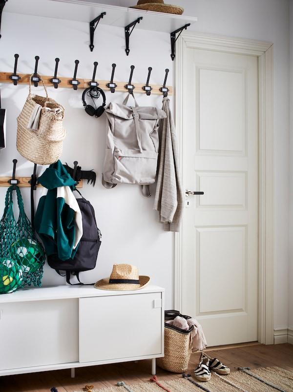 Une entrée avec une étagère murale blanche, des crochets noirs et un banc MACKAPÄR blanc à compartiments de rangement.