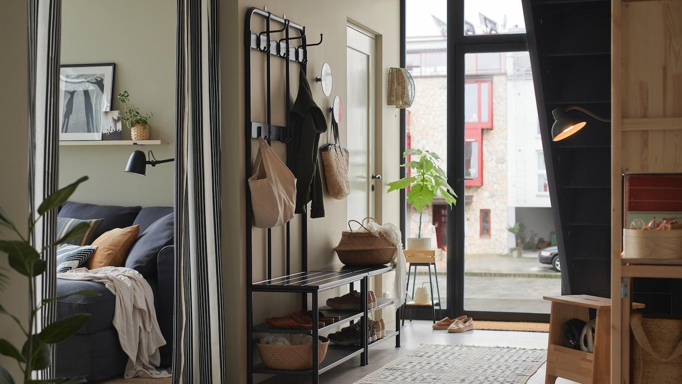Une entrée lumineuse avec un porte-manteau et porte-chaussures PINNIG contre un mur en face d'un escalier, chargé de sacs et de chaussures.