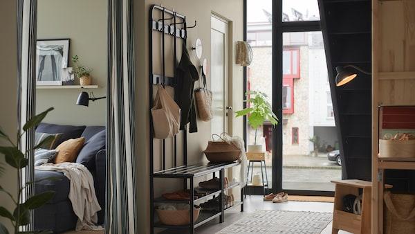 Une entrée lumineuse avec un portemanteau et range-chaussures PINNIG placé contre le mur faisant face aux escaliers et dans lequel sont rangés des sacs et des souliers.