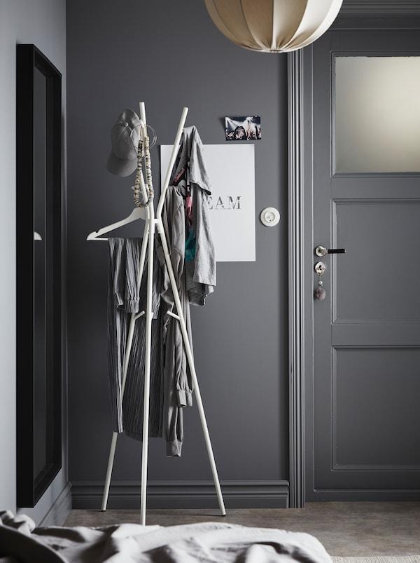 Une entrée peinte en gris avec une lampe blanche et un portemanteau EKRAR minimaliste blanc à trois pieds.