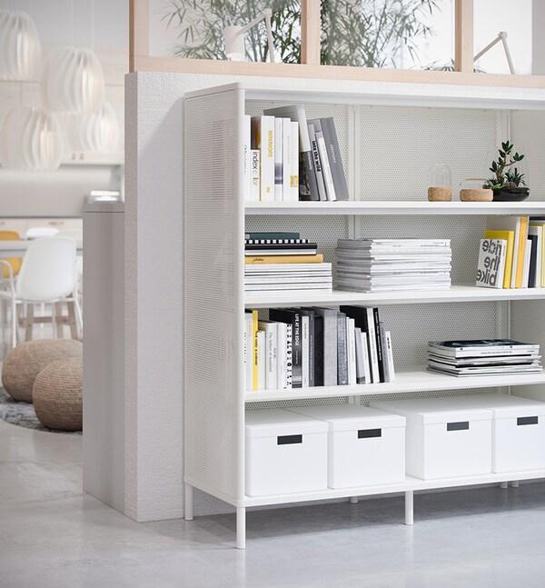 Une étagère blanche avec des livres et des boîtes de rangement