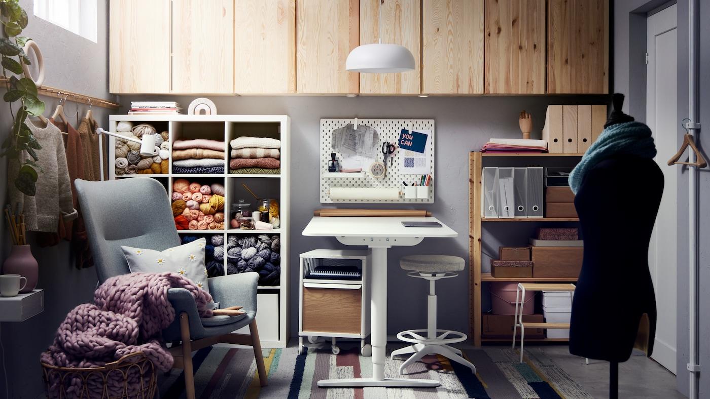 Une étagère blanche contenant des pelotes de laine, un fauteuil vert clair, un bureau blanc avec un tabouret assis/debout, des armoires en pin et une suspension.
