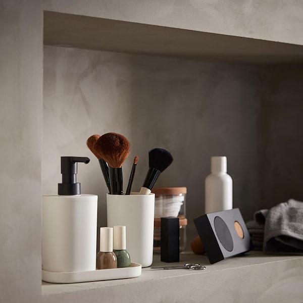 Une étagère de salle de bain avec des pinceaux de maquillage, un haut-parleur portable et divers articles de toilette.