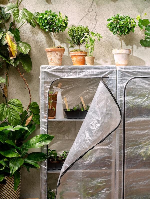 Une étagère en acier galvanisé HYLLIS remplie de plantes et recouverte d'une housse de plastique.
