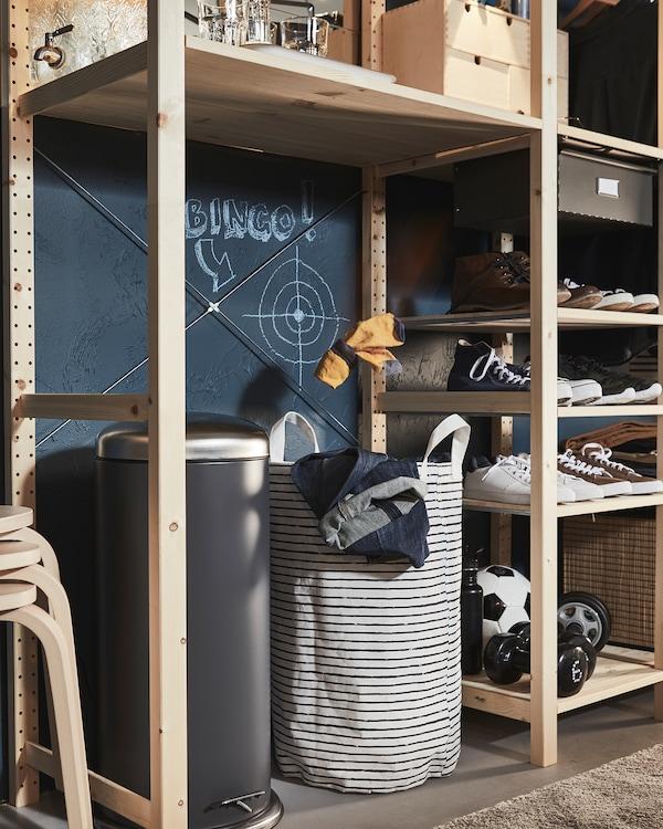 Une étagère en bois dans laquelle un grand trou accueille une poubelle et un sac à linge, une cible est dessinée au-dessus.
