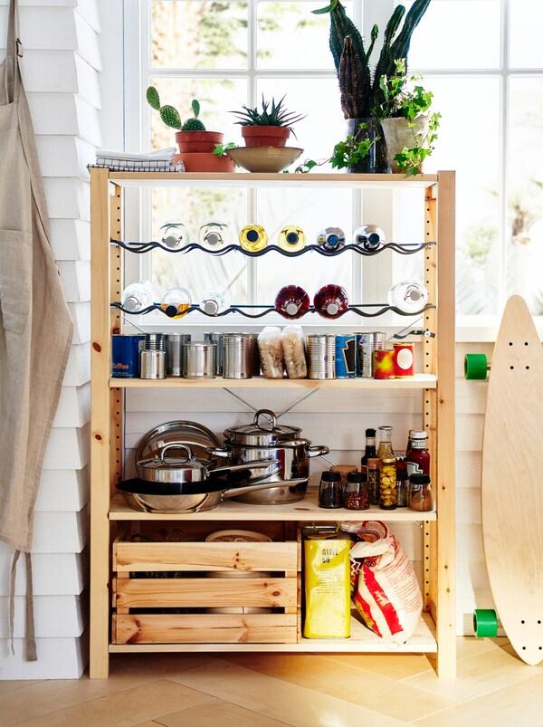 Une étagère IVAR est posée près d'une fenêtre, convertie en petit garde-manger avec des casseroles, des denrées sèches, de la nourriture en conserve et des bouteilles sur des supports.