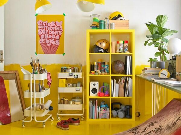 Une étagère KALLAX et deux dessertes RÅSKOG blanches font de pratiques espaces de rangement dans cette pièce jaune et blanche.