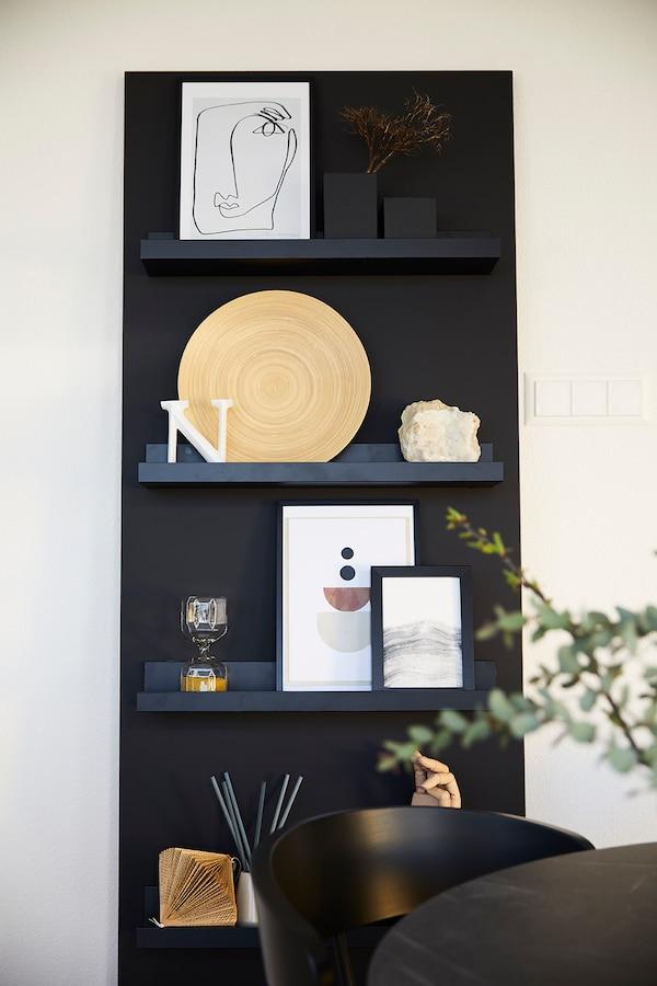 Une étagère noire avec des objets de décoration.