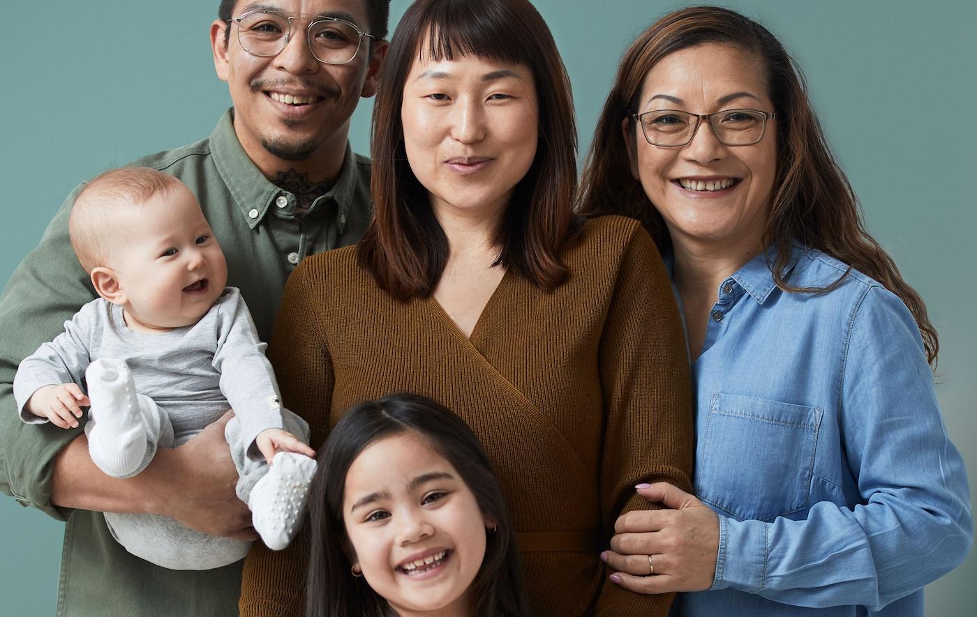 Une famille de cinq personnes ensemble, toutes souriantes: couple avec bébé, petite fille et grand-mère.