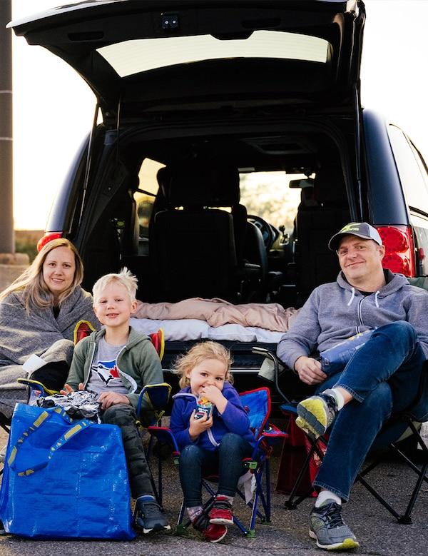 Une famille de quatre personnes est assise sur des chaises de camping derrière leur VUS, prête à regarder le film pendant la soirée ciné-parc.