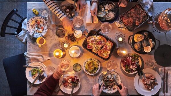 Une famille déguste un repas aux chandelles composé d'une variété de plats réconfortants disposés sur une table à manger.