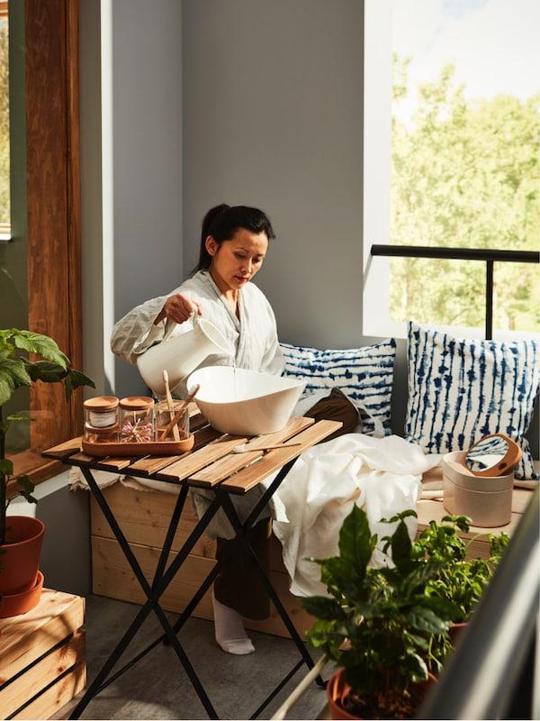 Une femme asiatique en peignoir verse l'eau d'une cruche blanche dans un bol sur une terrasse ou un balcon extérieur confortable.