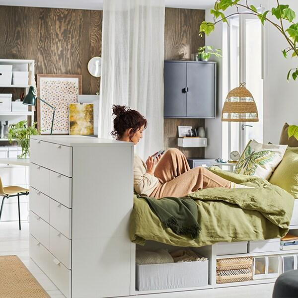 Une femme assise dans son lit utilise un appareil mobile.