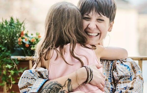 Une femme assise sur un balcon, portant une robe bleue à carreaux, un grand sourire aux lèvres avec une petite fille en robe rose dans les bras.