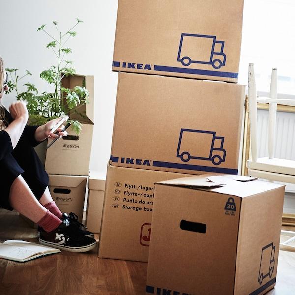 Une femme assise sur un plancher de bois entourée de boîtes de carton JÄTTENE.