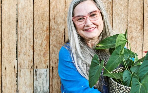 Une femme avec de longs cheveux gris et des lunettes à monture rose, portant une blouse bleue, sourit et tient une plante verte dans un pot en matière tressée.