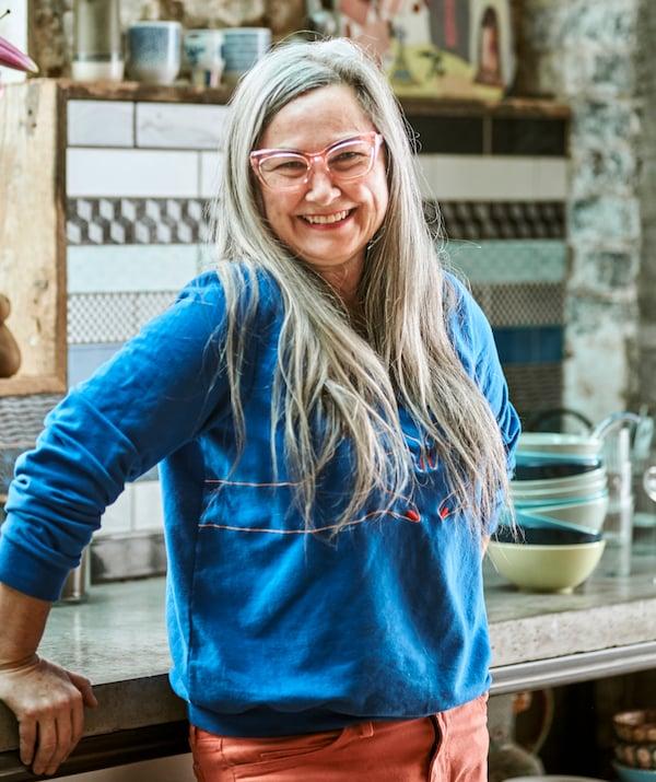 Une femme avec de longs cheveux gris et des lunettes à monture rose, une blouse bleue et un jeans rouge, souriant devant un plan de travail de cuisine.