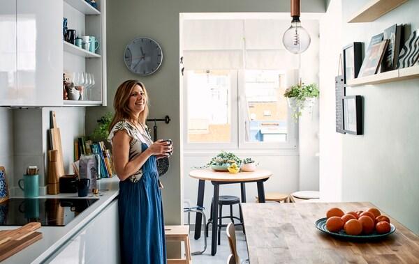 Une femme debout dans une cuisine étroite équipée d'armoires blanches et d'une table de bar en bois avec une petite salle à manger à l'extrémité de la cuisine.