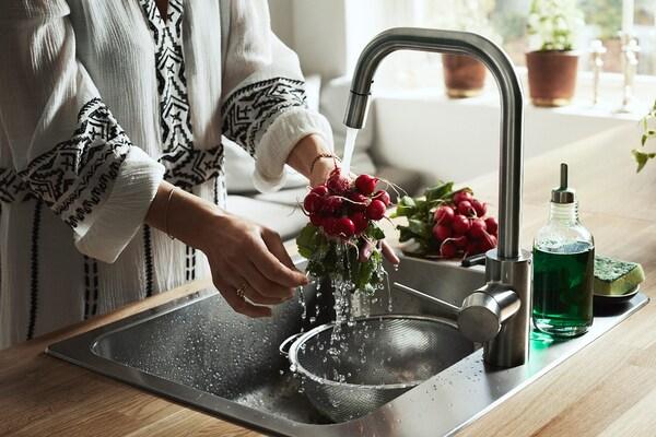 Une femme debout près de l'évier rinçant un bouquet de radis au robinet de cuisine ÄLMAREN.