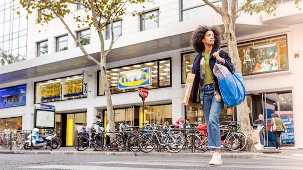 Une femme devant un magasin de meubles IKEA en ville, portant un sac bleu.