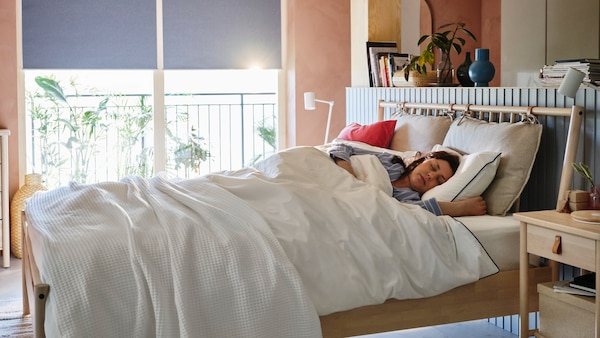 Une femme dort dans un lit BJÖRKSNÄS alors que la lumière du soleil entre par la fenêtre située derrière elle.
