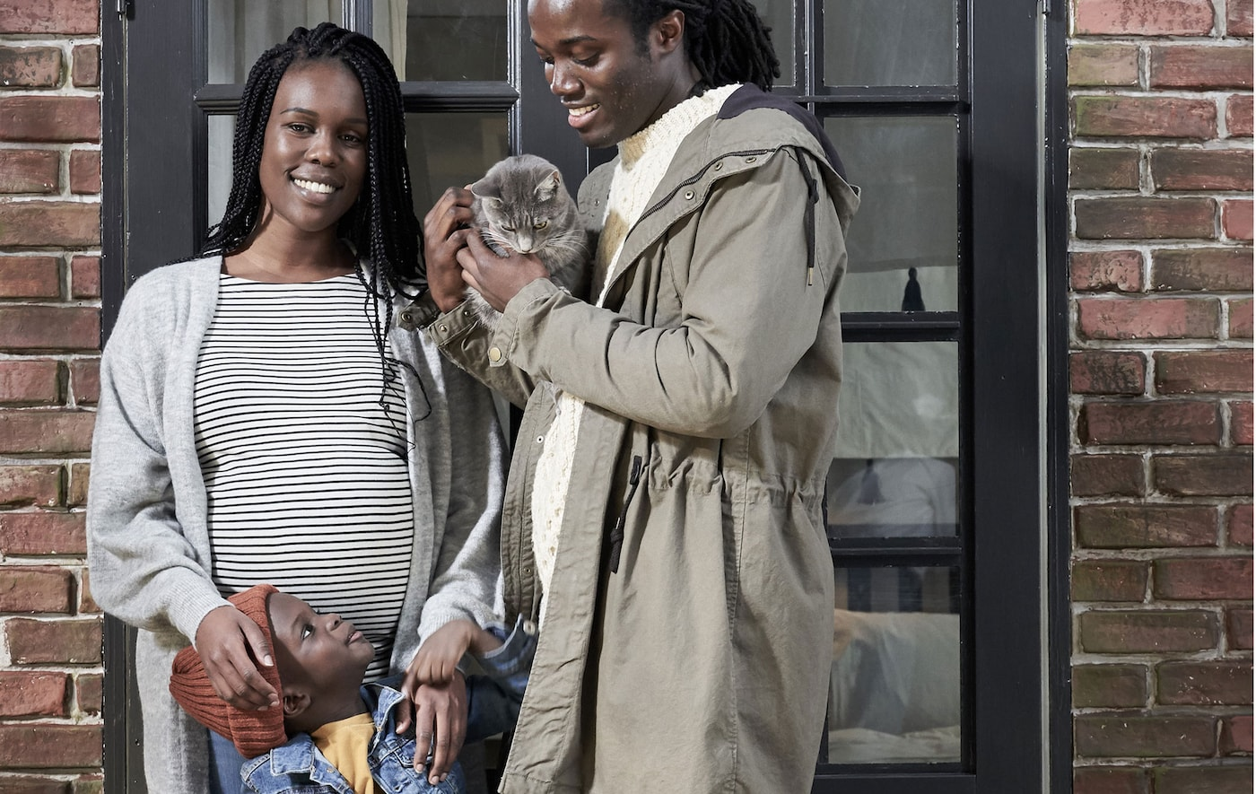 Une femme enceinte et un homme souriants, proches de la trentaine, devant un mur en briques, un petit garçon entre eux; l'homme a un chat dans les bras.