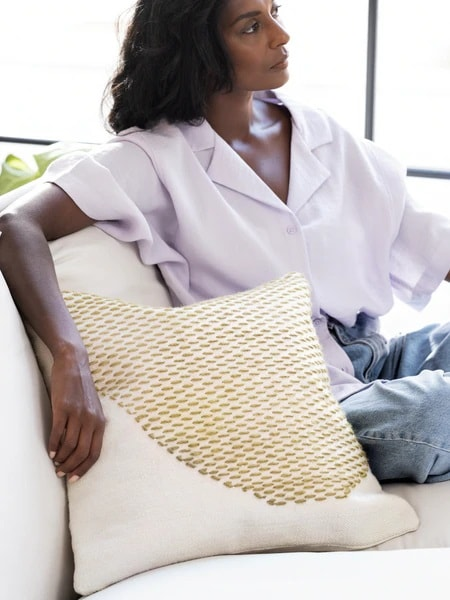 une femme est assise sur un canapé blanc avec un cousin blanc et jaune à motifs sus le bras