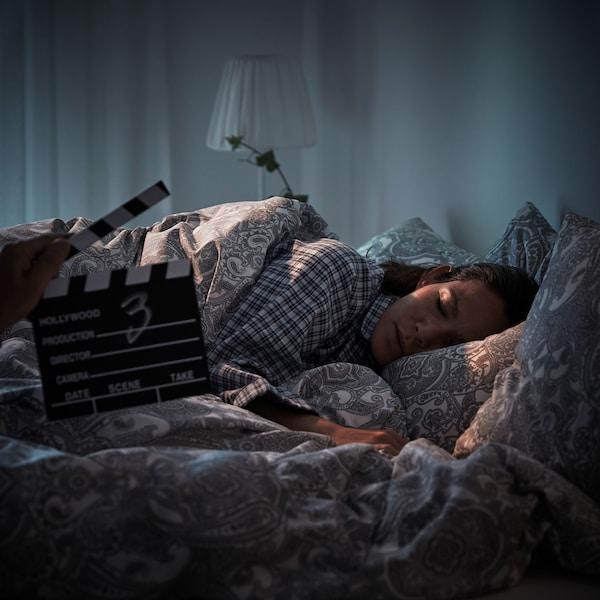 Une femme est endormie dans un lit face caméra alors qu'une main tient un clap de scène devant elle.